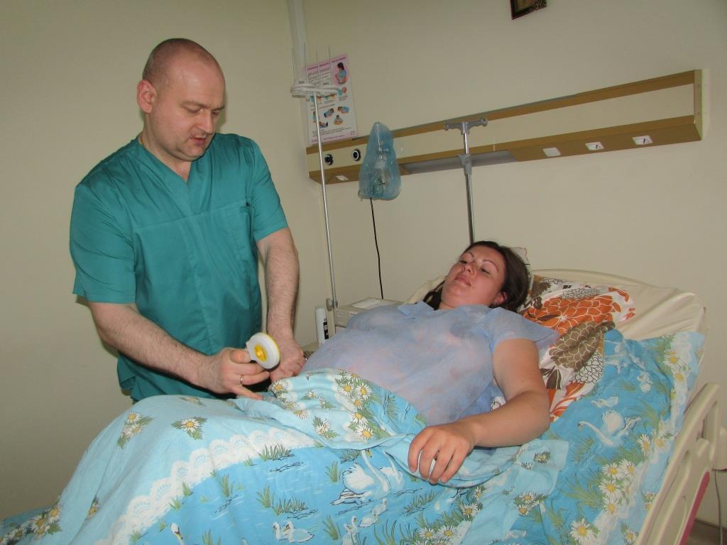 Микола Жиляєв, завідувач відділення патології вагітних вимірює серцебиття плода під час пологів. Народжує Христина Купен